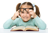 Cute little girl reads a book wearing glasses — Stock Photo