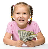 Cute cheerful little girl with paper money — Stock Photo