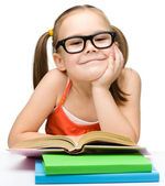 Cute little girl is reading book — Stock Photo