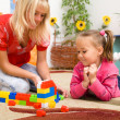 Photo: Teacher and child are playing with bricks