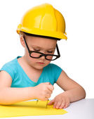 Little girl is playing while wearing hard hat — Stock Photo