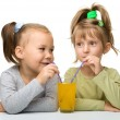 Two little girls are drinking orange juice — Stock Photo #8356594