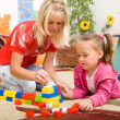 Foto Stock: Teacher and child are playing with bricks