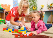 Teacher and child are playing with bricks — Stock Photo