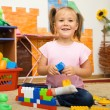 Little girl is playing with toys in preschool — Foto de stock #8363426