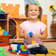 Little girl is playing with toys in preschool — Stock fotografie