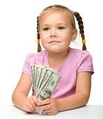可爱的小女孩用纸钱-美元 — 图库照片