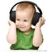 Cute boy enjoying music using headphones — Stock Photo