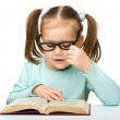 Little girl reads a book while wearing glasses — Stock Photo