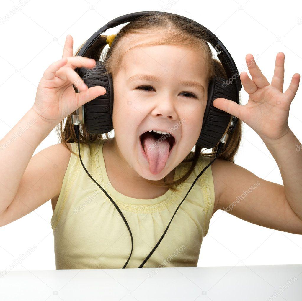 可爱的小女孩享受音乐使用头戴式耳机和显示她的舌头,白上孤立— 照片