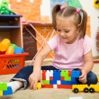 Little girl is playing with building bricks — Stock Photo #9426059