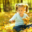 Cute little girl is playing with leaves in park — Stock Photo #9426091