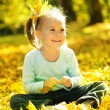 Cute little girl is playing with leaves in park — Stock Photo #9426100