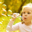 Little girl is blowing a soap bubbles — Stock Photo #9426181