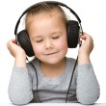 Cute little girl enjoying music using headphones — Stock Photo