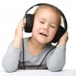 Cute little girl enjoying music using headphones — Stock Photo