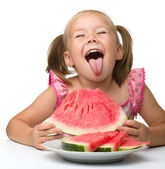 Cute little girl is gungy to eat watermelon — Stock Photo