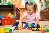 Little girl is playing with building bricks — Stockfoto