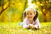 Cute little girl is playing with leaves in park — Stok fotoğraf