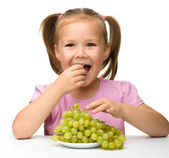 Little girl is eating grapes — Stock Photo