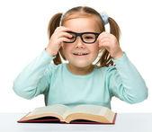 Cute little girl reads a book — Stock Photo