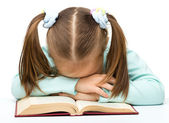 Cute little girl is sleeping on a book — Stock Photo