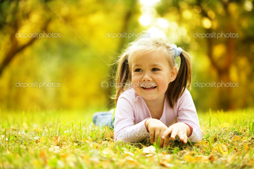 Cute little girl is playing with leaves in autumn park — Stock Photo #9426157