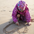 Girl drawing a heart in sand — Photo