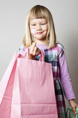 Little girl with shopping bags and lollipop — Stock Photo
