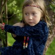 Little girl sitting on a branch of an apple tree — Stock Photo