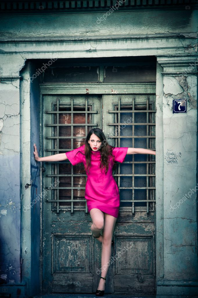 Elegant woman in pink dress and high heels stand in entrance doors of an old building, full body shot  Stock Photo #10567944