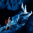 Young woman with backpack exploring huge cave with torch — Stock Photo