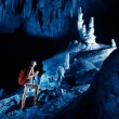 Stock Photo: Young womwith backpack exploring huge cave with torch