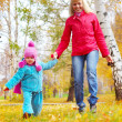Happy young mother and her little daughter having fun in an autumn park — Stock Photo