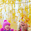 Happy young mother and her little daughter having fun in an autumn park — Stock Photo #8148854