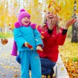 Stock Photo: Happy young mother and her little daughter having fun in an autumn park