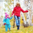 Happy young mother and her little daughter walking in an autumn park - Stock Photo