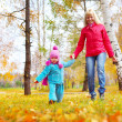 Happy young mother and her little daughter walking in an autumn park — Stock Photo