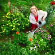 Woman watering her garden - Stock Photo