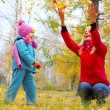 Young mother and her little daughter having fun in an autumn forest — Stock Photo