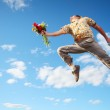 Man jumping with flowers and gift box — Stock Photo