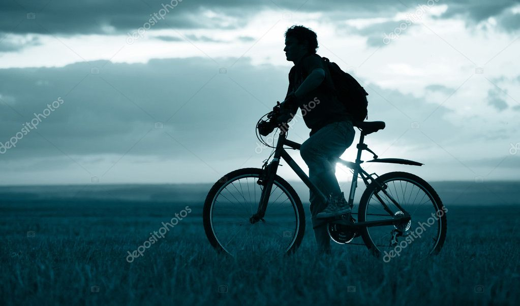 Man with bicycle standing on field on sunset background — Stock Photo #8147599