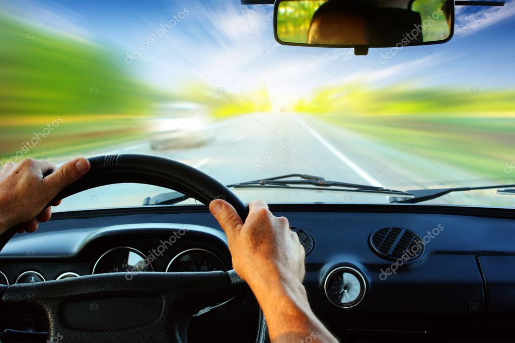 Hands on steering wheel of a car driving on an asphalt blurred road — Stock Photo #8147609