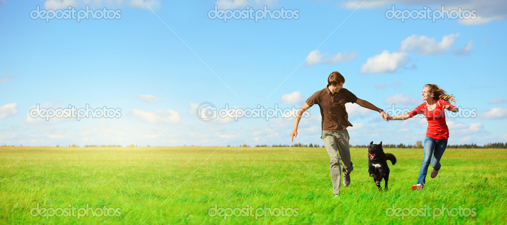 Young happy lovers runnung with a dog on meadow with green grass and blue sky  Stock Photo #8147757