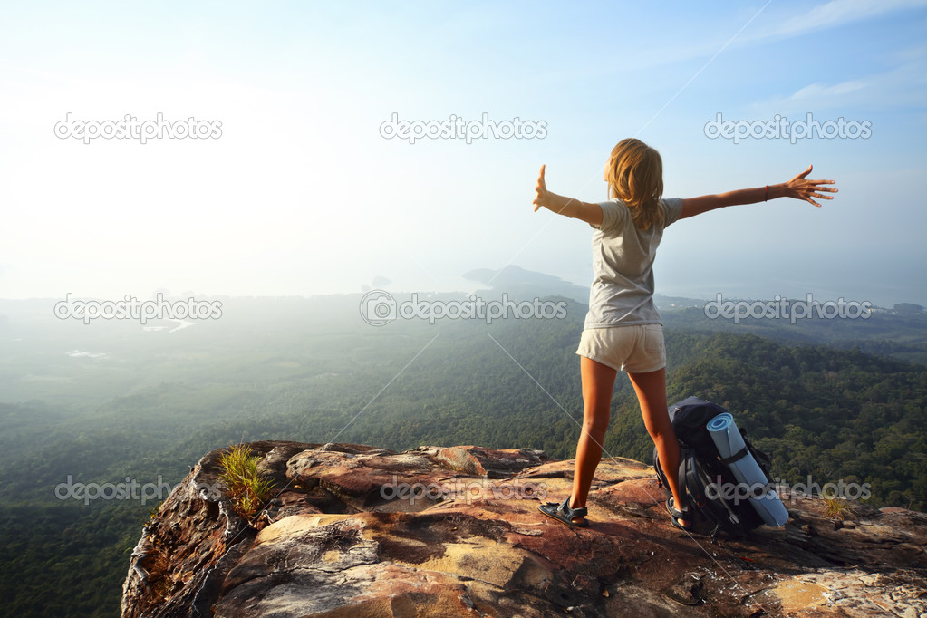 Young woman with backpack standing on cliff's edge and looking to a sky with raised hands — Stock Photo #8147888