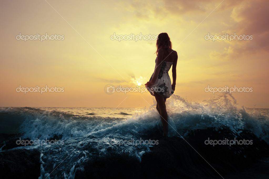 Young woman standing on a rock in sea and holding her dress. Toned  Stock Photo #8148246