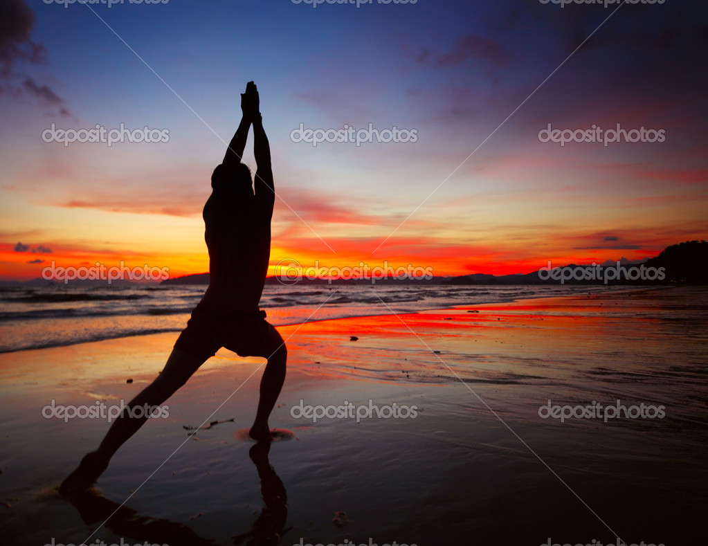 Young men doing exercises on wet sand — Stock Photo #8148375