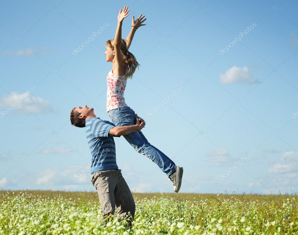 Young man and woman having fun on countryside meadow with herbs and flowers — Stock Photo #8148846
