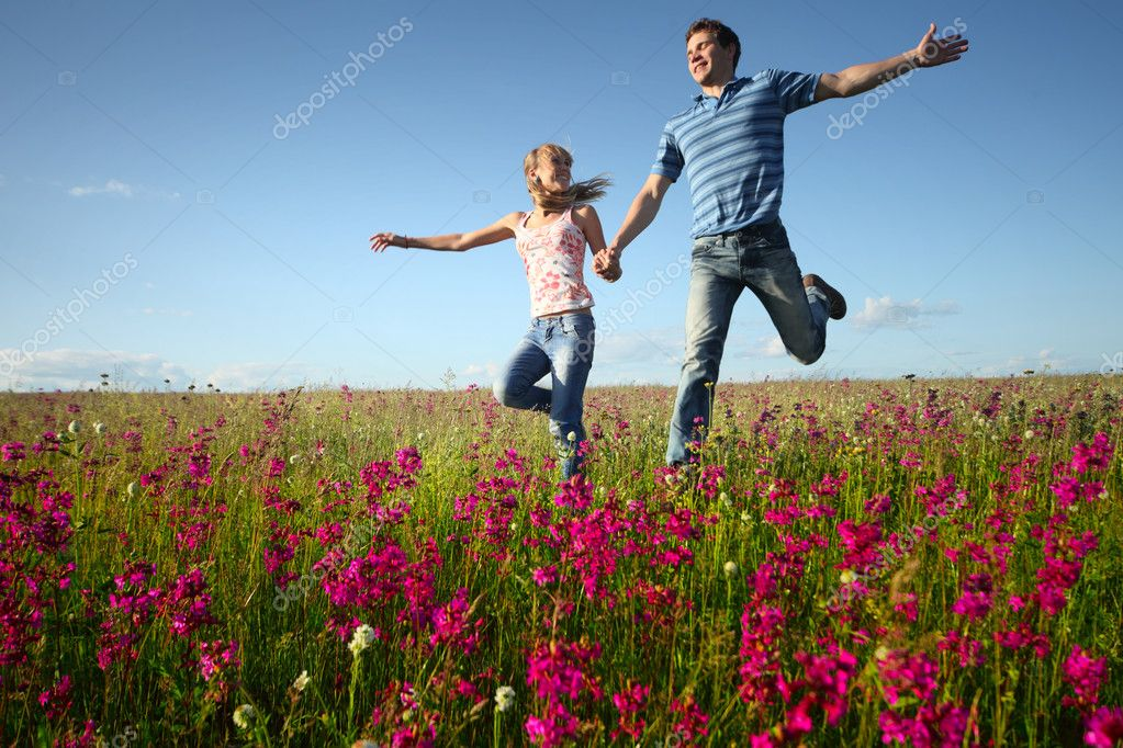 Young man and woman rinning on countryside meadow with pink flowers — Stock Photo #8148878