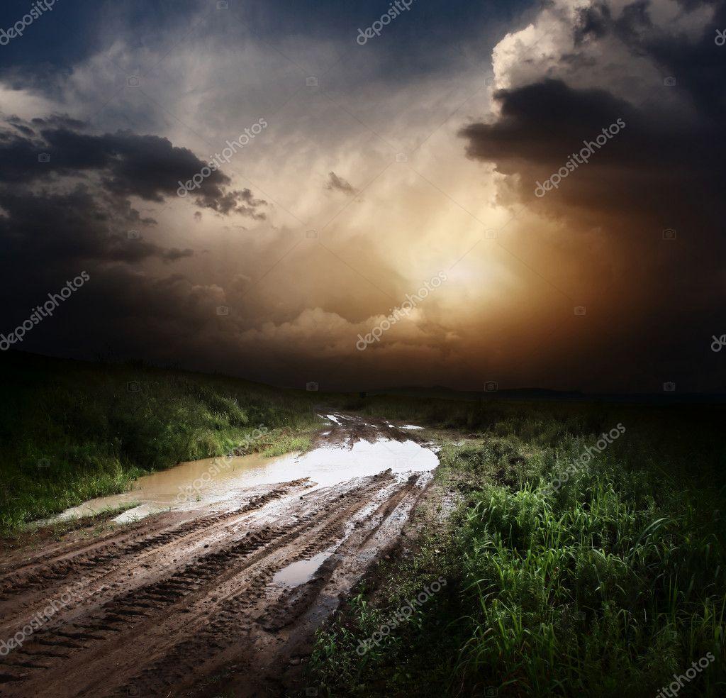 泥泞湿的农村道路和风暴乌云